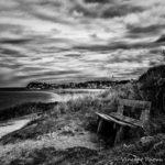 photographie noir et blanc d'un banc à la mer